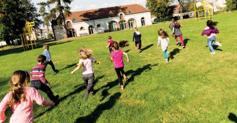 Photo avec 11 enfants de dos, ils courent dans l'herbe vers un batiment au loin, la journée est ensoleillée