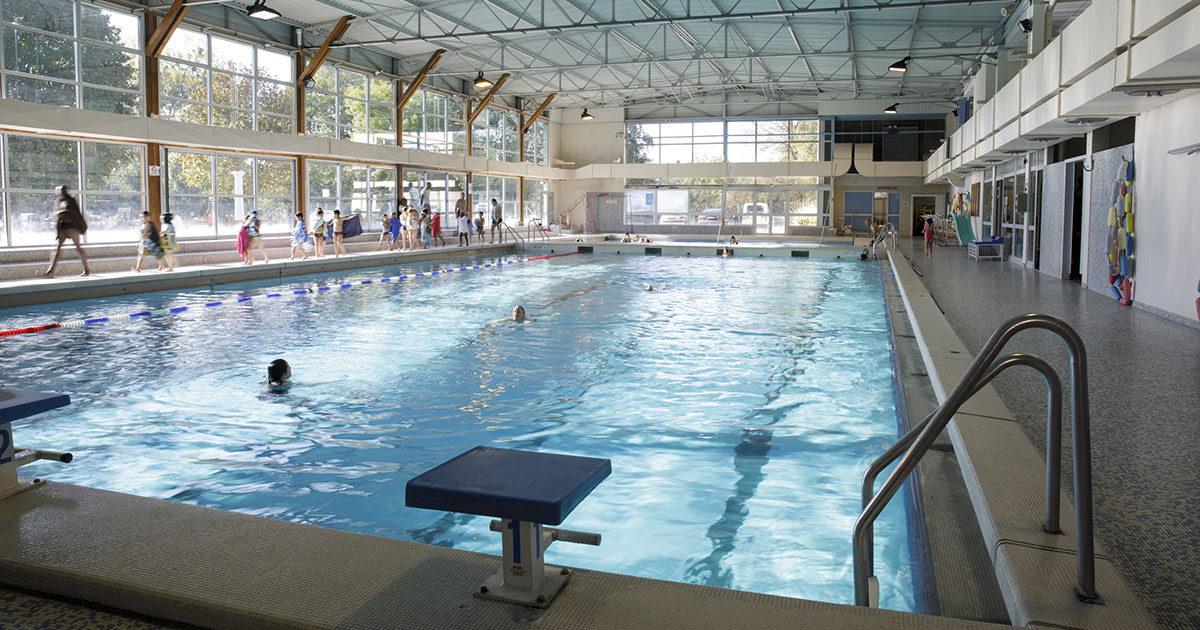 Interieur de la piscine de vernouillet, avec des personnes dans l'eau et autour du bassin