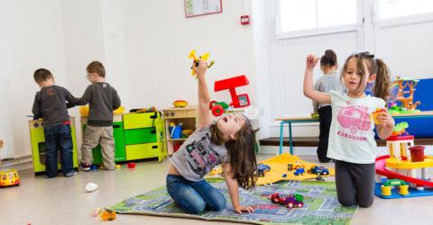 Des enfants jouent au sein d'une structure, énormément de jouets dans la pièce