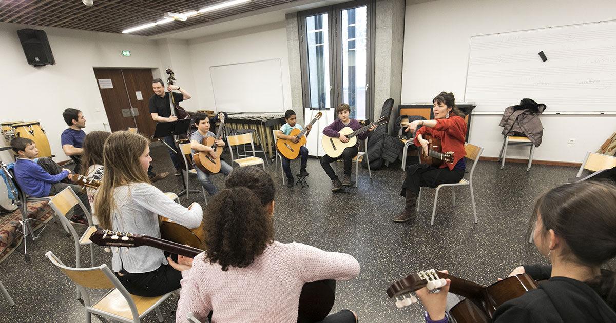 Des eleves accompagnes par leur professeur, jouent de la guitare