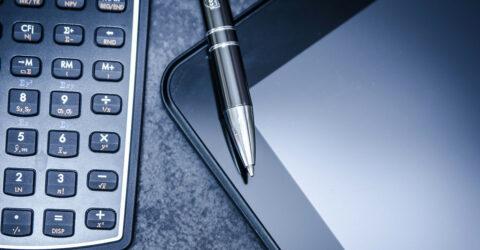 Photo avec une calculatrice, un stylo et une tablette