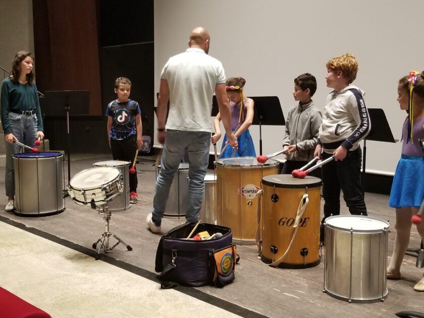 Professeur avec des eleves jouent d'un instrument