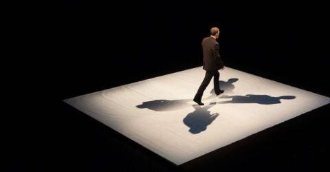 Basile NARCY, un homme marche seul dans le noir, sous les lumieres des projecteurs