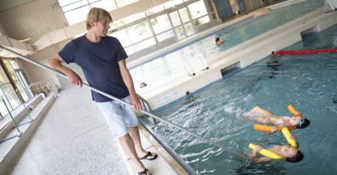 Maitre nageur au bord de la piscine avec deux enfants qui nagent sur le dos